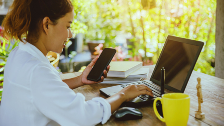 asian woman sitting at table. sitting working in the holiday is laptop, smartphone and cup of coffee.On computer screen. Stock Photo