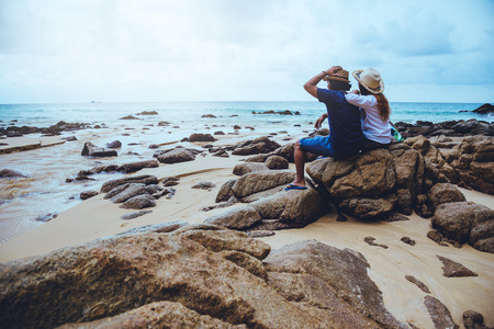 Asian lovers happy on the beach.The sky is bright Travel nature and sitting relax on the rocks at the sea at phuket. in Thailand. summer.