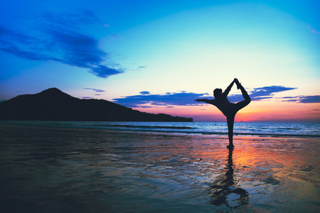 Young woman yoga at the beach happy exercise summer. Stok Fotoğraf