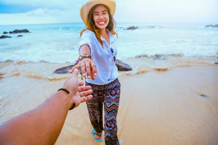 Asian lovers happy travel nature on the beach. Couple running on a sandy beach.Travel relax in summer