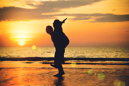 Asian lovers happy on the beach with a beautiful sunset in background man lifting the woman.