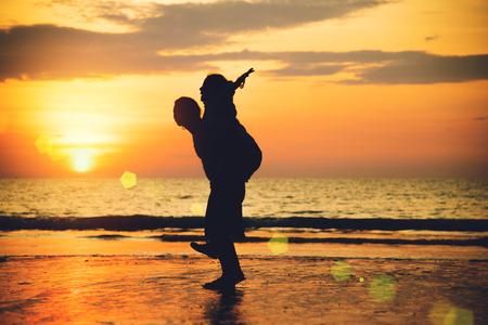 Aziatische geliefden blij op het strand met een prachtige zonsondergang op de achtergrond man die de vrouw optilt.