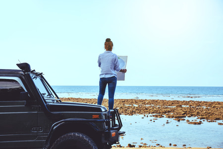 Asian woman travel nature. Travel relax. Stand on the car and In the map handle at the beach.In the summer. Thailand