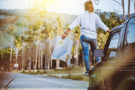 woman travel relaxing nature mountain map navigation. Stand on the car and In the map handle.