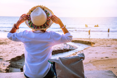 Asian woman travel nature. Travel relax. Sitting see the sunset on the beach. In the summer