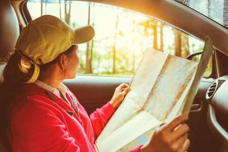 Asian women travel relax in the holiday. Traveling by car park. View map for Nature tours during the rainy season.