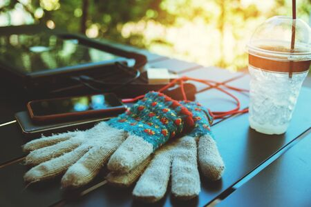 travel nature, Travel relax, Work on a laptop at a coffee shop in winter, with cold gloves on the table. Stock Photo