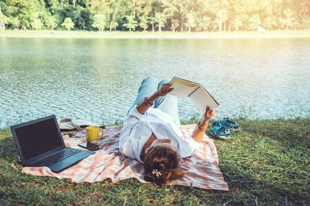 Women sitting a relax working with a notebook and lying reading a book during a relax in the park. in the holiday. summer Standard-Bild