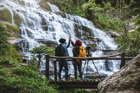 couples travel relax to photograph the waterfalls beautiful. In the winter. at the waterfall mae ya chiangmai in thailand. travel nature. summer