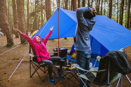 young asian couple of happy enjoying Camping in the pine forest Sit and eat food at the Camping page in the midst of nature.