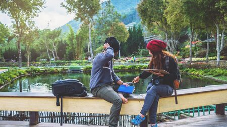 Asian couple travel photograph nature education. nature relax and study read a book. at public park. In Thailand