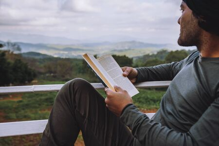 Man traveler is reading book travels nature on the mountain In the fresh air in the north, Chiang Mai in Thailand.