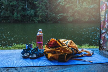 Travel nature. travel relax. Backpack and shoes mobile phone with a traveler.sun set placed in front of the tent camping. Background of mountain lake nature.
