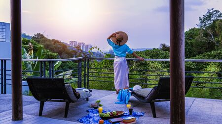 A happy woman is standing at the landscape view. Relax on the terrace at home in the summer. On holiday, drink wine, orange juice and fruit at sunset. Imagens