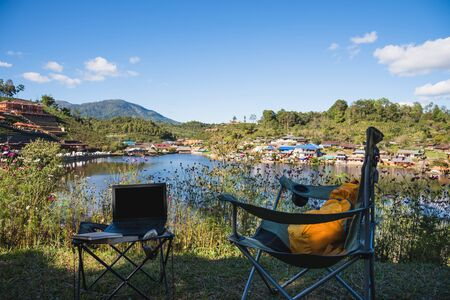 Adventures Camping and And use a working notebook near lake, Concept Travel, Camping Ban Rak Thai village Mae Hong Son in Thailand. Stock fotó