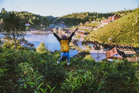 The girl enjoyed and enjoyed his travels. She laughed and jumped in the tea plantation. Travel nature in village countryside.