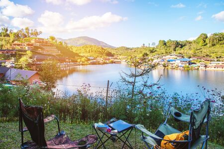 Adventures Camping and And use a working notebook near lake, Concept Travel, Camping Ban Rak Thai village Mae Hong Son in Thailand. Фото со стока