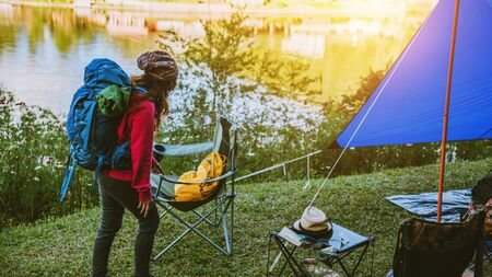 Travel camping on the mountain in rural villages, close to the lake, Asian women tourist relaxing holidays.in Thailand