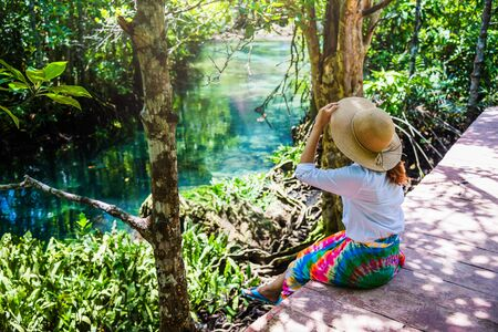 Asian women travel relax, travel nature in the holiday. Nature Study in the forest. women happy enjoying sitting and watching the lake mangrove forest. tha pom-klong-song-nam at krabi. summer Stock fotó