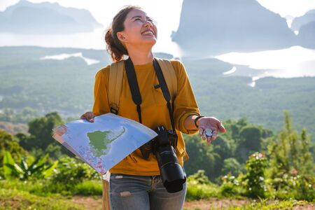 Female travelers are holding a map with money fifteen baht. The concept of tourism has little money can travel. The girl who laughs and is happy travel adventure. Travel Thailand.