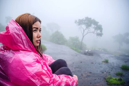 Girl with pink rain coat Sitting View the scenery natural beautiful forest touch fog. travel nature, Travel relax, Travel Thailand, rainy season. (Phu Hin Rong Kla National Park)