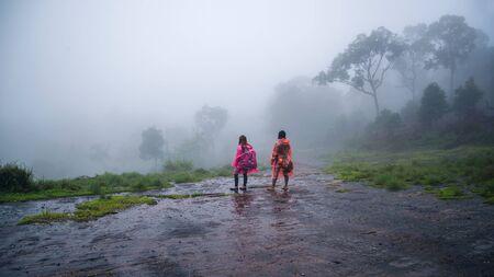 couples tourist with rain coat walking travel adventure nature in the rain forest. travel nature, Travel relax, Travel Thailand, rainy season, Happy, romantic.