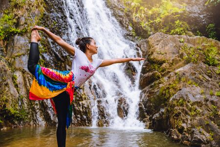 Asian women relax in the holiday. Play if yoga.  Play if yoga at waterfall On the Moutain. exercise, good health, travel nature, Travel relax. Travel Thailand. ( Huai Toh waterfall ) Banco de Imagens