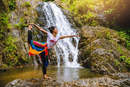 Asian women relax in the holiday. Play if yoga.  Play if yoga at waterfall On the Moutain. exercise, good health, travel nature, Travel relax. Travel Thailand. ( Huai Toh waterfall ) 写真素材