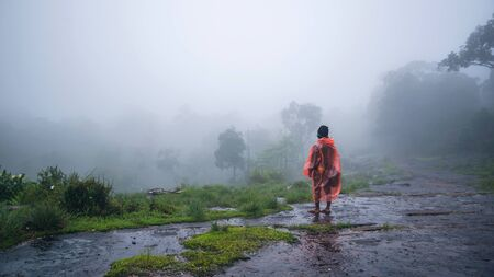 tourist with rain coat walking travel adventure nature in the rain forest at Phu Hin Rong Kla National Park. travel nature, Travel relax, Travel Thailand, rainy season.