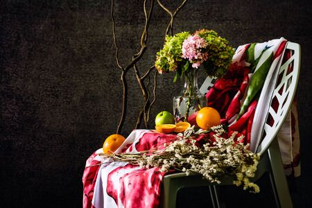 Hydrangeas flowers that are placed in a vase, and white flowers. with Fabric, red flowers that lie on the chair. Photo background flowers, fruit Style Vintage. Apple, Orange, grape 版權商用圖片