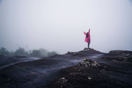 tourist with pink rain coat Stand View the scenery natural beautiful touch fog at Phu Hin Rong Kla National Park. travel nature, Travel relax, Travel Thailand, rainy season. Stock fotó
