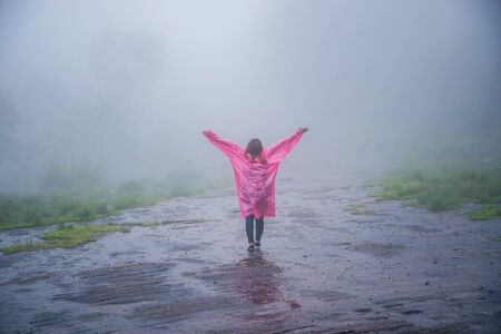 tourist with pink rain coat Stand View the scenery natural beautiful touch fog at Phu Hin Rong Kla National Park. travel nature, Travel relax, Travel Thailand, rainy season.