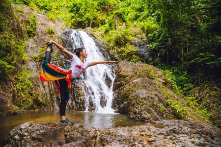 Asian women relax in the holiday. Play if yoga.  Play if yoga at waterfall On the Moutain. exercise, good health, travel nature, Travel relax. Travel Thailand. (Huai Toh waterfall)