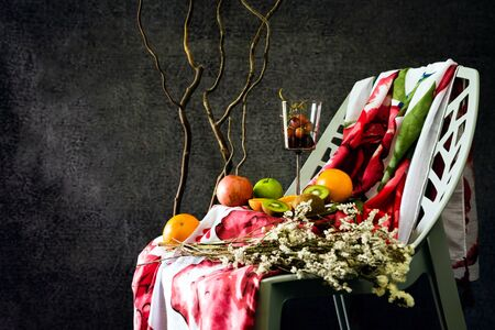 White flowers and purple flowers placed on the fabric. with Fabric, red flowers that lie on the chair. Photo background flowers, fruit Style Vintage. Apple, Orange, grape, Fruit kiwi, Side view.