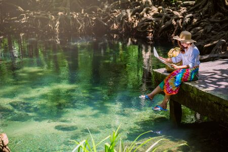 Asian women travel relax, travel nature in the holiday. women enjoying Sitting and watching the travel map the lake mangrove forest. tha pom-klong-song-nam at krabi. summer, Map