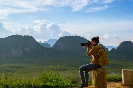 Young woman travels to take pictures of nature on the mountain. Travel adventure. Landscape Beautiful Mountain on sea at Samet Nangshe Viewpoint. Phang Nga Bay, Travel Thailand, summer holiday.