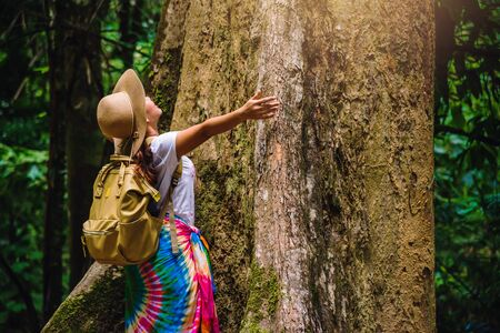 A girl with a backpack is embracing a big tree. enjoying  travel nature in the forest Lush green trees. In the summer, Travel relax, Travel Thailand, tourist, countryside, outdoor, rain forest. Stock fotó