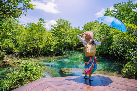 A young traveler girl relax in the holiday enjoying the beauty of nature lake mangrove forest at tha pom-klong-song-nam at krabi. summer, Travel, Thailand, freedom, Attractions.