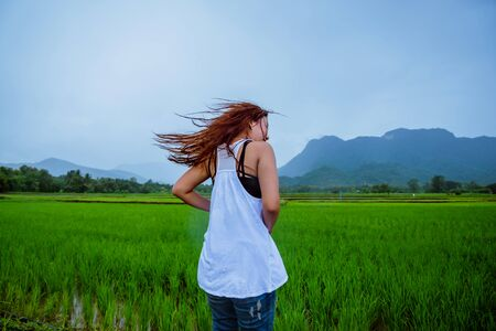 Asian women travel relax in the holiday.The girl smiled happy and enjoyed the rain that was falling. travelling in countrysde, Green rice fields, Travel Thailand.