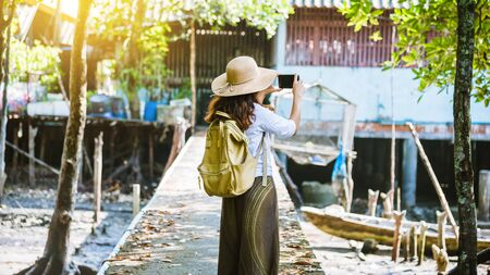 The Girl tourists walking taking pictures The way of life of the villagers in rural villages Ban Bang Phat - Phangnga. summer, lake, holiday, travel Thailand. backpack. Mobile phone, photograph. Stock fotó