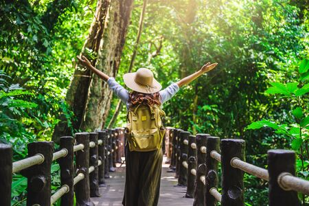 The girl is happy to travel to the mangrove forest. She is walking on the bridge and raising her hand. Nature trail, Than Bok Thorni Waterfall. Relax, Travel, Backpack, Nature, Tourism, Rural, Style.