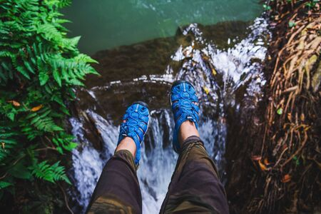 Asian woman travel nature. Travel relax. Top view of the girls legs wearing blue shoes. She is lifting her legs floating on the waterfall. nature, background, summer, holiday, tourist.