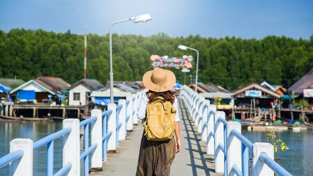 Girl traveler with backpack walking over bridge on the lake Tourism in rural villages Ban Bang Phat - Phangnga. Asian woman travel nature. Travel relax. travel Thailand. summer, holiday, tourist. Stock fotó