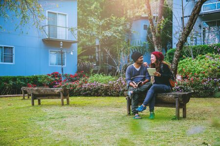 Asian couple smiled and was happy with the book read. Among the beautiful flower gardens, Valentine Standard-Bild