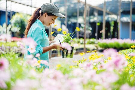 Happy young woman working in a greenhouse, writing notes and studying the growth of trees.