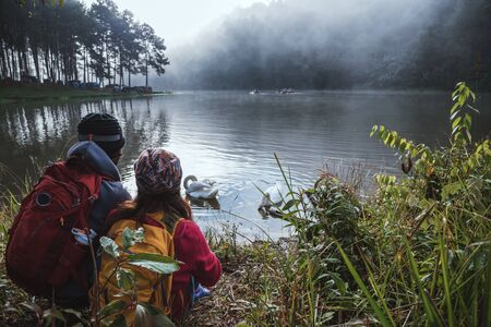 Asian couples are watching the swan, gracefully in a reservoir Pang Ung, Mae Hong Son, Thailand. 版權商用圖片 - 127639492