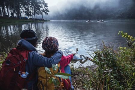 Asian couples are watching the swan, gracefully in a reservoir Pang Ung, Mae Hong Son, Thailand. 版權商用圖片 - 127639693
