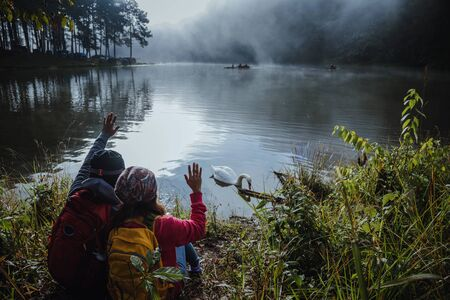 Asian couples are watching the swan, gracefully in a reservoir Pang Ung, Mae Hong Son, Thailand.