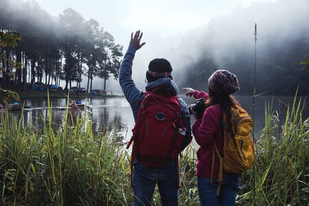 Couple lovers travel beatiful nature panorama view of Pang Ung lake in the mist at sunrise, Mae Hong Son province, Thailand. 版權商用圖片 - 127639744