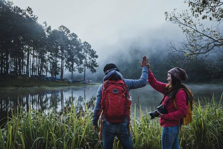 Couple lovers travel beatiful nature panorama view of Pang Ung lake in the mist at sunrise, Mae Hong Son province, Thailand.